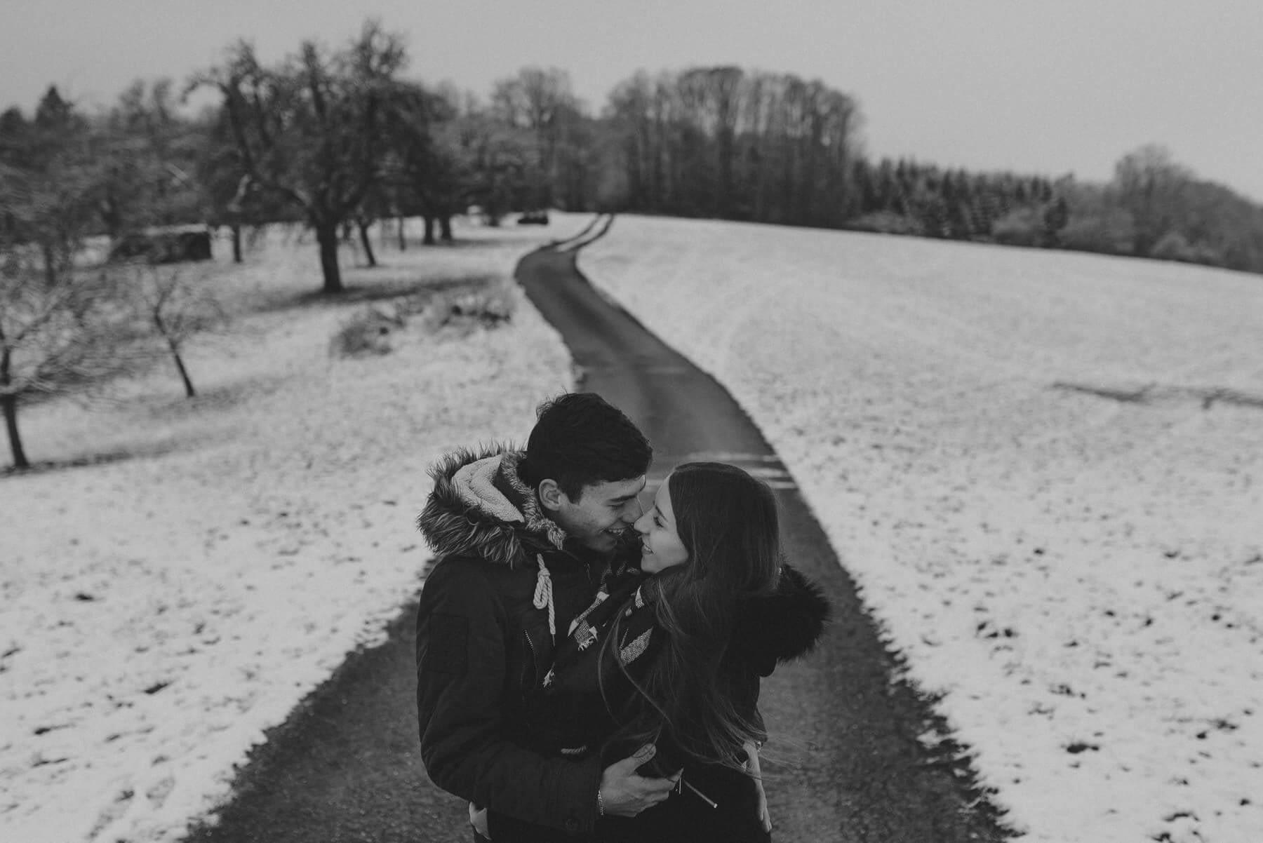 Lachendes Paar während Shooting auf Straße und Feldweg im Schnee