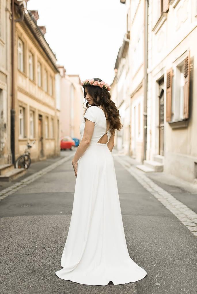 Braut mit Hochzeitskleid von Ivy & Oak Bridal aus Berlin in einer Gasse in der Altstadt Bamberg