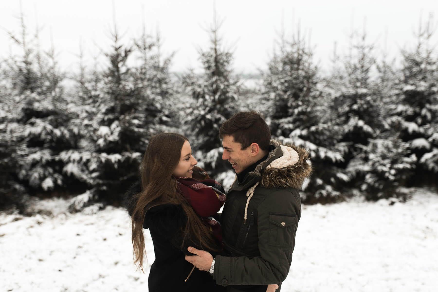 Verliebtes Paar lachend im Schnee vor Nadelwald mit Umarmung