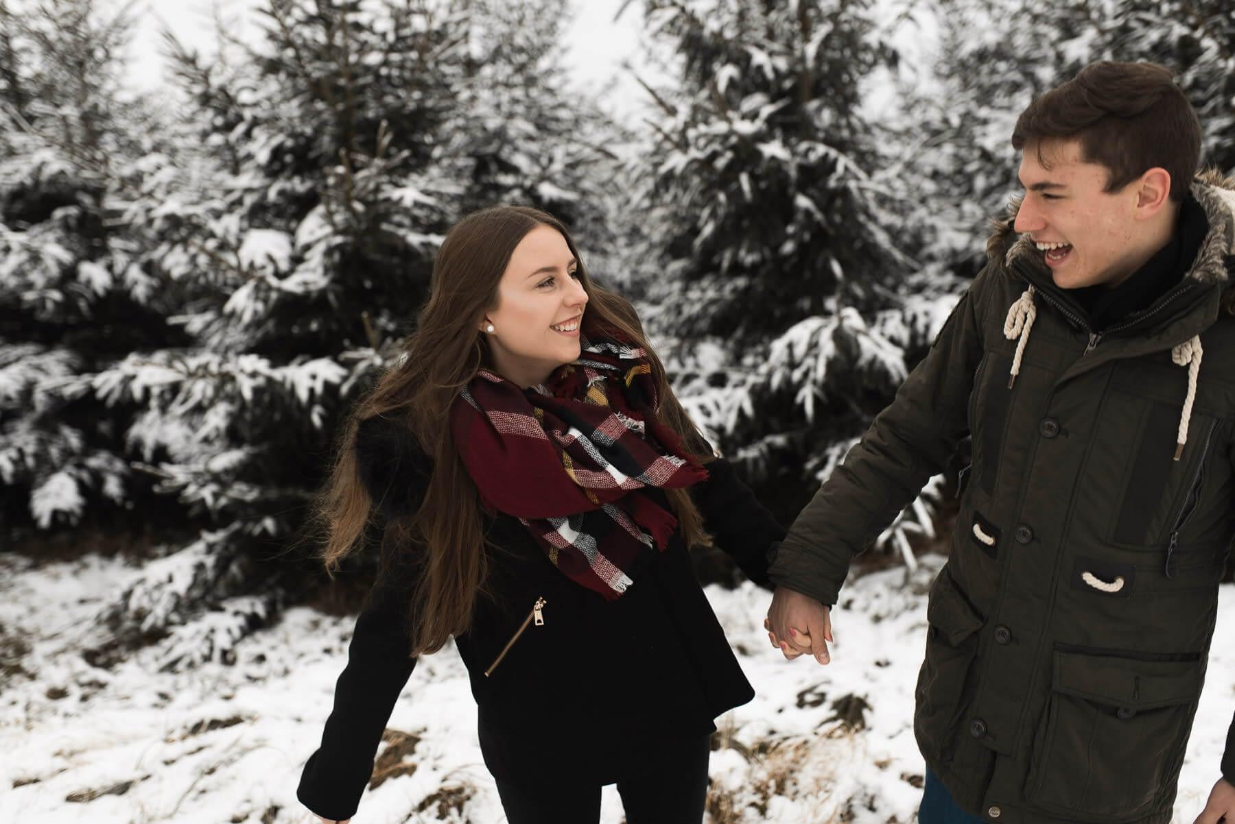 Lachendes Paar im Winter im Wald nach Schneefall