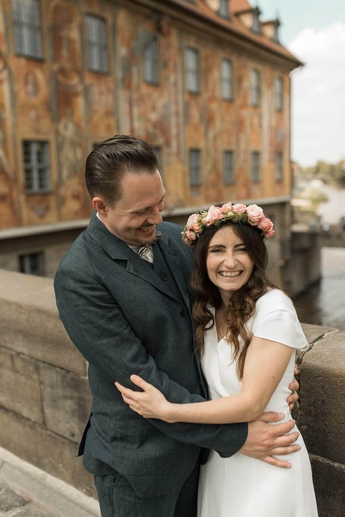 Lachendes Brautpaar auf oberer Brücke mit alten Rathaus im Hintergrund