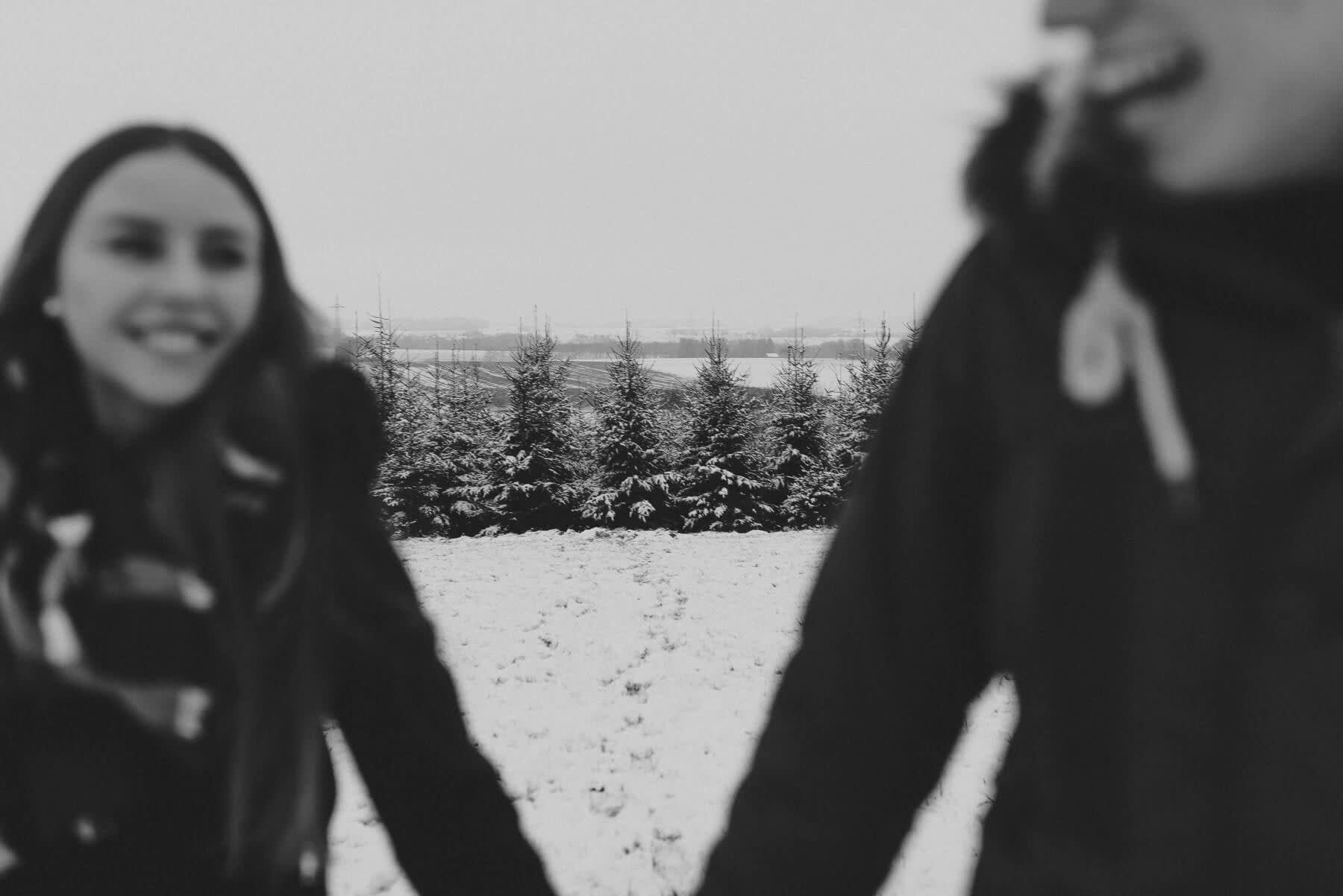 Lachen während dem Wintershooting im Nadelwald unscharf und in Schwarz weiß