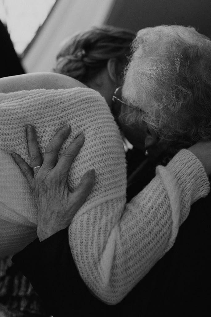 Oma im Rollstuhl umarmt Braut nach Trauung im Heldensaal
