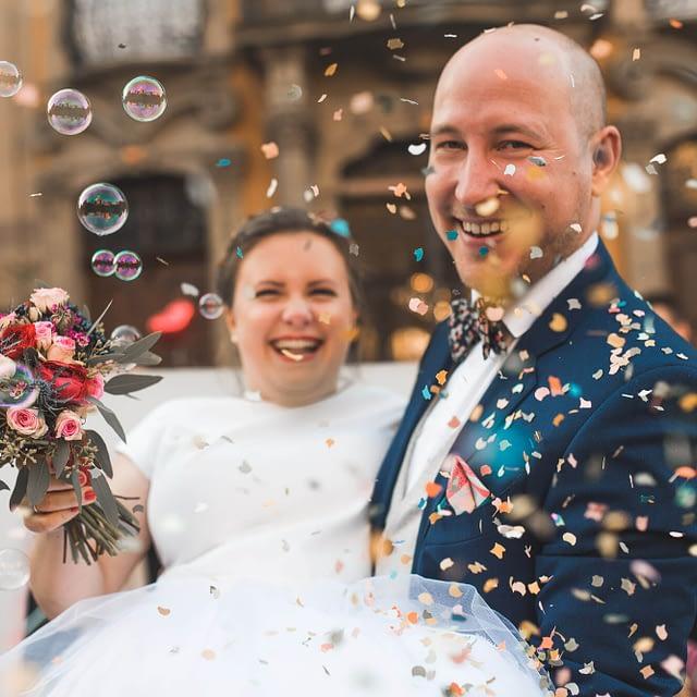 Brautpaar im Konfettiregen bei Standesamt Trauung in Schwäbisch Hall mit Seifenblasen und lachenden Gesichtern bei Winterhochzeit